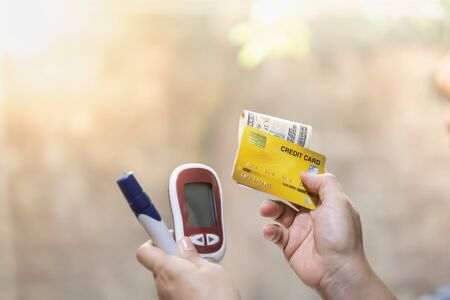 Close up of woman holding Glucose meter, lancet, credit card and US dollars banknote. Use as Money, Medicine, diabetes, glycemic, health care and people concept. Banque d'images