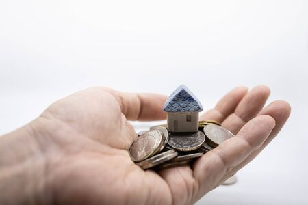 Home Loan, Business and Finance concept. Close up of mini toy house on top of pile of coins on man hand with white background and copy space. Standard-Bild