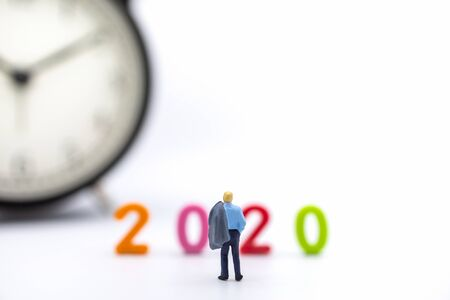 Business and 2020 New Year Planning Concept. Close up of businessman miniature figure people with jacket standing on white background and looking to colorful plastic number and vintage round clock with copy space. Imagens