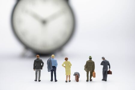Voyage d'affaires et concept de temps. Gros plan d'un groupe d'hommes d'affaires et de femmes miniatures avec valise debout et regardant vintage horloge ronde sur fond blanc et espace de copie.