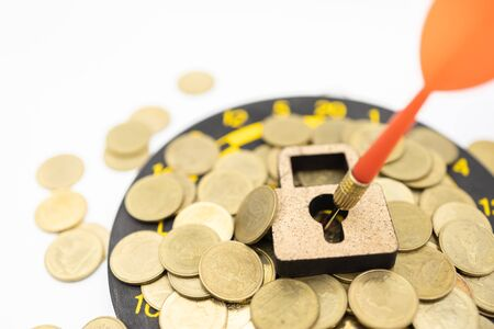Business, Money Security, Planning, Target Concept. Close up of wooden master key icon with dart stab on center of board with pile of gold coins on white background and copy space.