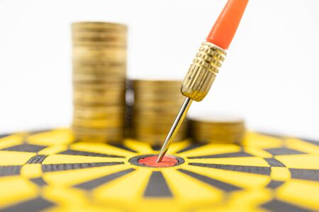 Money, Game, Business, Planning and Target Concept.  Close up of dart stab on center of black and yellow board with stack of gold coins on white background. Banco de Imagens - 128797348