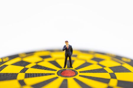 Business, Planning, Target and Goal Concept. Close up of businessman miniature figure standing close to center of  dart board with white background and copy sapce. Banco de Imagens