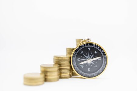 Succession, Finance, Business, Money, Security, Planning and Saving Concept. Close up of compass with stack of gold coins on white background and copy space. Banco de Imagens - 128797441
