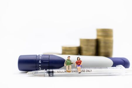 Fat man and woman miniature figure sitting on insulin syringe with lancet for control diabetes blood sugar level with stack of gold coins. Use for Medicine,  glycemia, health care, money and people concept.