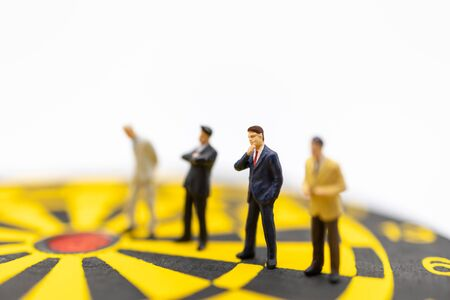 Business, Planning, Succession and Management Concept. Close up of group of businessman miniature figure standing and thinking on yellow and black dart board on white background. Banco de Imagens - 128797456