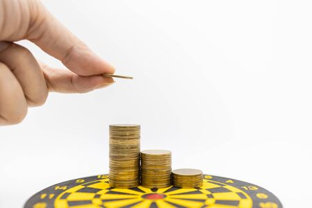 Business, Money, Planning and Saving Concept. Close up of man hand holding a gold coin and put it on top of stack of coins on black and yellow dart board on white backgtound and copy space