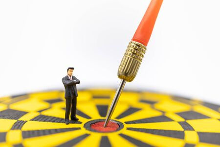 Business, Planning, Target and Goal Concept. Close up of businessman miniature figure standing and looking to dart stab on center of black and yellow board with white background and copy sapce. Banco de Imagens - 128797577