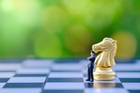 Business, Planning, Global, work and strategy concept. Close up of businessman miniature figure standing and thinking on chessboard with gold knight chess piece and green nature background.