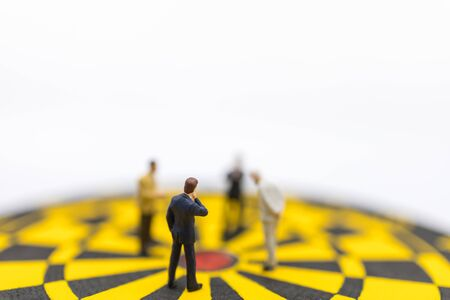 Business, Planning, Succession and Management Concept. Close up of group of businessman miniature figure standing and looking to center of yellow and black dart board on white background. Banco de Imagens - 128797794