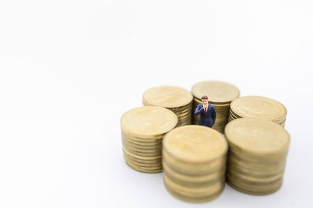 Business, Money, Finance and management concept. Close up of businessman miniature figure standing center of row of stack of gold coins on white background and copy space. Banco de Imagens - 128846425
