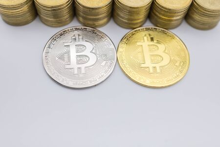 Money, Finance, E-Commerce and cryptocurrency Concept. Close up of silver and gold Bitcoin coin with stack of coins and copy space.