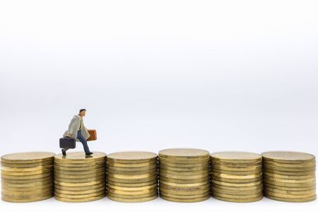 Business, Money, Finance and management concept. Close up of businessman miniature figure with baggage running on top of row of stack of gold coins.