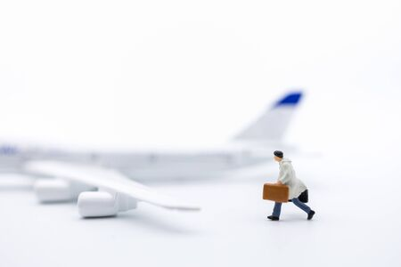 Business Travel and transportation Concept. Close up of businessman traveler miniature figure with baggage running on white background with mini toy airplane model and copy space for text. Stock Photo
