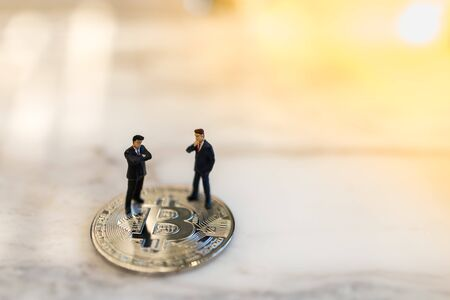 Business, e-commerce, crypto currency, finance and technology concept. Close up of two businessman miniature figure standing on bitcoin coin on ground with copy space.