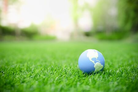 Global Warming, Environment and Ecology Concept. Close up of mini world ball on green grass lawn with rain drop.