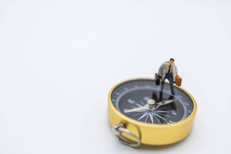Business Trip, Planning and Direction Concept.  Close up of businessman miniature people with handbag and suitcage walking on compass on white background and copy space.