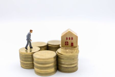 Business, Money, Finance, Home loan and management concept. Close up of businessman miniature figure walking on top of stack of gold coins to mini wooden house toy on white background.
