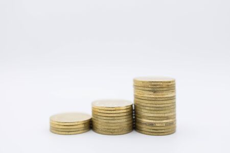 Money, Business and Saving Concept. Close up of stack of used and old gold coins on white background and copy space. Banco de Imagens