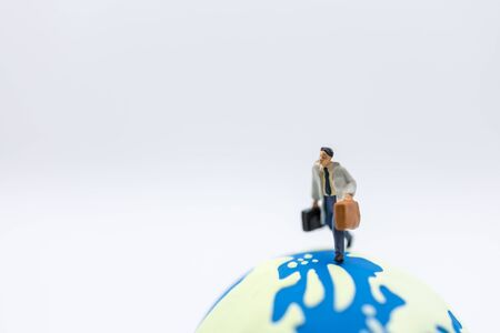 Business Travel and Global Concept. Close up of businessman traveler miniature figure with baggage running on mini world ball on white background Banco de Imagens