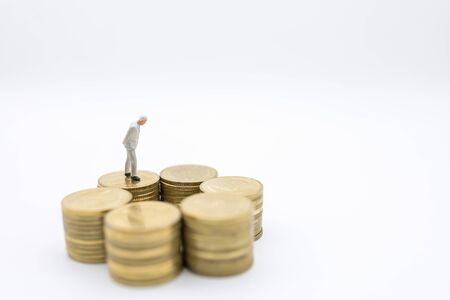 Business, Security, Retirement and saving concept. Close up of old businessman miniature figure walking on top of stack of gold coins on white background.