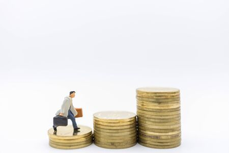Business, Money, Finance and management concept. Close up of businessman miniature figure with baggage running to top of stack of gold coins. Banco de Imagens
