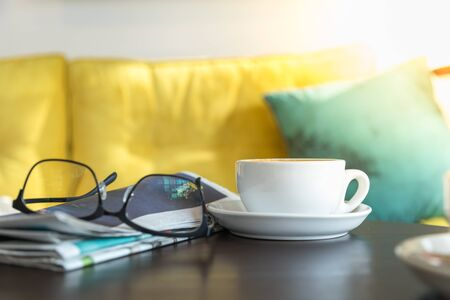 Close up of white cup of hot coffee latte with newspaper and reading glasses on wooden table in restaurant. Banco de Imagens