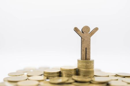 Business, Finance, Money Saving and Success Concept. Close up of wooden man figure  on top of stack of gold coins on white background with copy space.