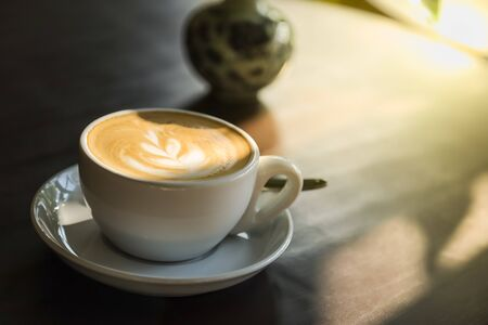 Close up of white cup of hot coffee latte with milk foam art with plate and spoon on wooden table with morning sunlight and shadow. Banco de Imagens