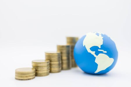 Global Business, Money and Saving concept. Close up of mini world ball with stack of gold coins on white background.