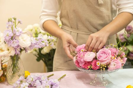 Close up of young woman arranging beautiful pink rose flower bouquet vase on table. Stock Photo