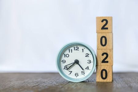 2020 new year and time concept. Close up of round clock and stack of wood number blocks on wooden table and white background. Stok Fotoğraf