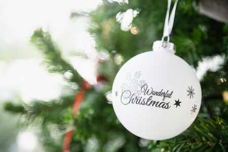 Happy New Year, Christmas and Holiday Season Concept. Close of white snow flake pattern ornament ball on xmas tree with copy space. Stockfoto