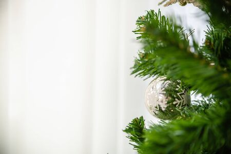 Happy New Year, Christmas and Holiday Season Concept. Close of silver snow flake ornament ball on xmas tree with copy space. Stockfoto