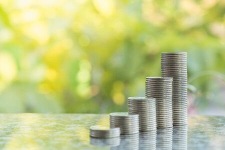 Business, Money, saving and security concept. Close up of stack of silver coins with bokeh of green leaf nature background and copy space.