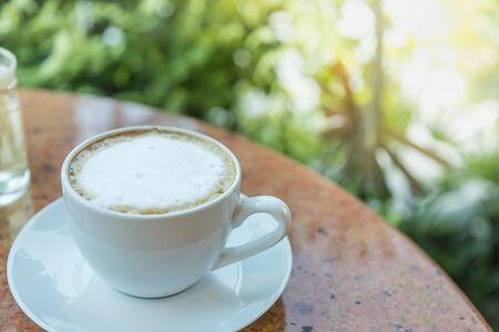 Nahaufnahme von weißer Tasse und Teller mit heißem Latte-Kaffee auf rundem Tisch und grünem Blattnaturhintergrund.