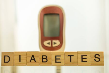 Close up of wooden letters block wording and Glucose meter as background using as Medicine, diabetes, glycemia, health care and people concept. Stock fotó