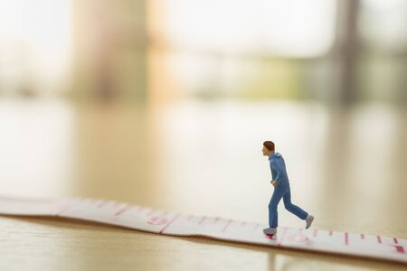 Sport and fitness concept. Close up of man runner miniature figure people running on measure tape on wooden table with copy space Stock Photo