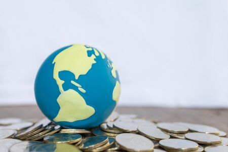 Global Business and Financial Concept. Close up of world mini ball on pile of coins on wooden table and copy space.