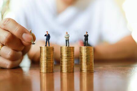 Geschäfts-, Geld- und Personalmanagement-Ressourcenkonzept. Nahaufnahme der Hand des Mannes, die Geschäftsmann Miniaturfigur Menschen hält und die Figur auf den Stapel von Goldmünzen auf Holztisch setzt. Standard-Bild