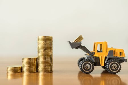 Business, Money,  Finance and Saving  Concept. Close up of miniature mini loader truck contain 4 coins and puting to top of stack of gold coins on wooden table with copy space. Zdjęcie Seryjne