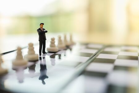 Business, Teamwork and Strategy Planning Concept.  Close up of businessman miniature people figure standing on chessboard between pawn chess pieces and copy space. Zdjęcie Seryjne