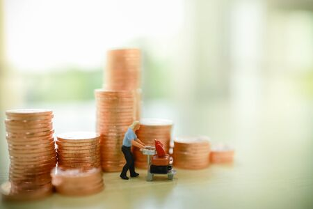 Business, Travel, Money and saving concept. Close up of traveler miniature figure people with airport trolley and suitcase with stack of copper coins on wooden table.