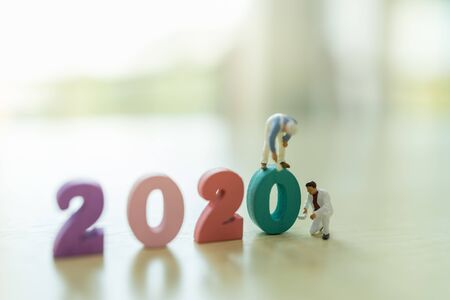 2020 New year, Business and Planning Concept. Close up of group of worker miniature figure painting and cleaning colorful wooden number with copy space
