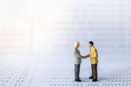 Business, Money, Financial and cooperation concept. Close up of two businessman miniature figures people meeting and hand skake on bank passbook with copy space.