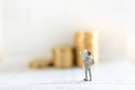 Business, Money, Saving, Security and Family Concept. Close up of father and child standing on bank passbook and looking to stack of gold coins with copy space. Zdjęcie Seryjne
