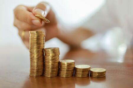 Geschäft, Geld, Finanzen, sicheres und sparendes Konzept. Nahaufnahme der Hand des Mannes, die zwei Münzen hält, um Goldmünzen auf einem Holztisch zu stapeln.