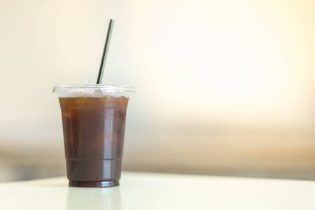Close up of take away plastic cup of iced black coffee (Americano) on table with copy sapce.
