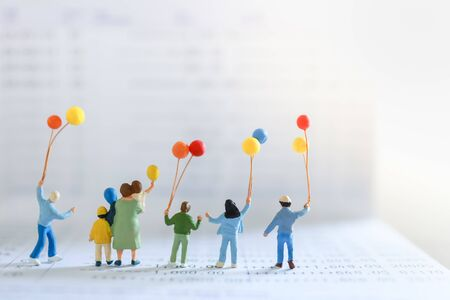 Business, Money, Finance and Family Concept. Group of children and kid miniature figure people with colorful balloon standing on bank passbook with copy space. Zdjęcie Seryjne