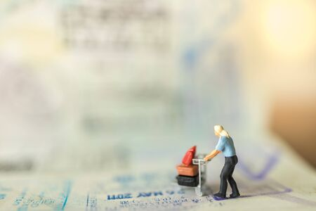 Travel Concept. Male traveler miniature figure people with baggage on airport trolley walking on passport with immigration stamps and VISA.
